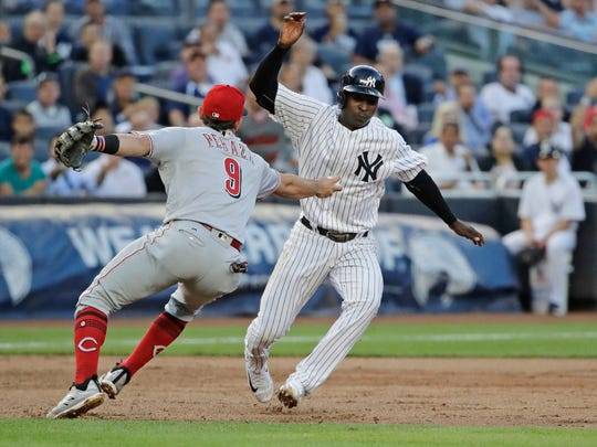 Reds shortstop Jose Peraza tags out Didi Gregorius