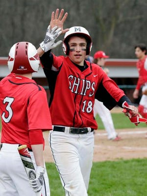 Manitowoc's Bryce Fischer (3) greets Tanner Halder (18) after scoring against Sheboygan South Tuesday at Wildwood Baseball Park.