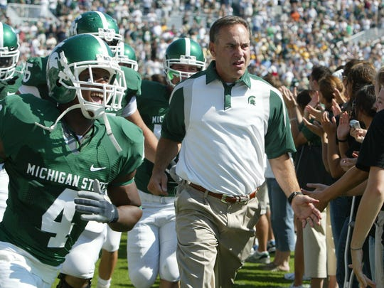 Mark Dantonio, right, leads MSU players onto the field before the start of his first game as coach, a 55-14 in over UAB on Sept. 1, 2007 in East Lansing.
