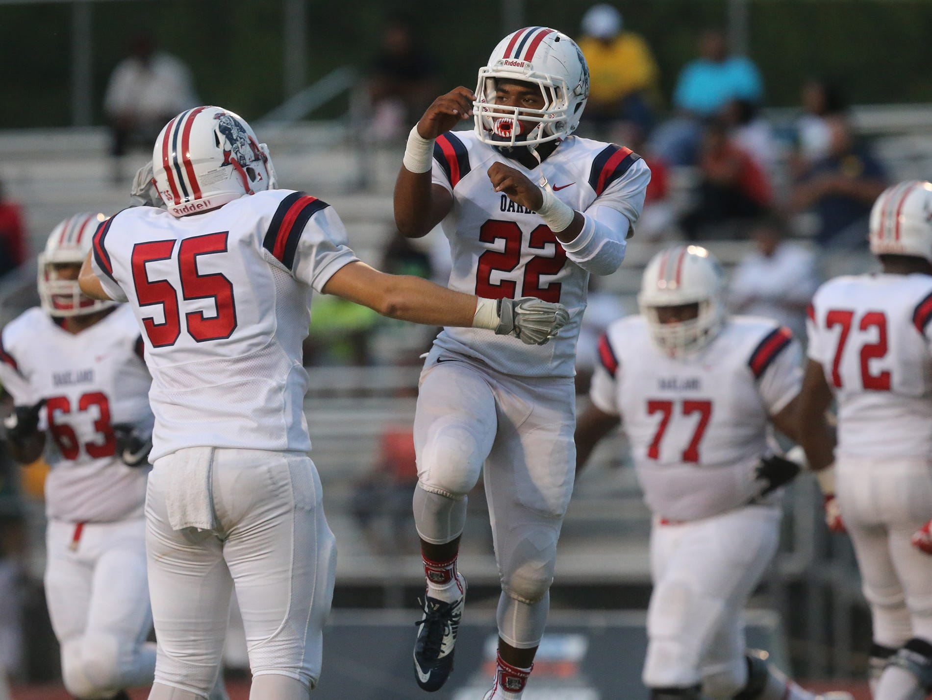 Oakland's Michael Roper (22) and Thadd Chapman (55) celebrate Oakland's first touchdown of the night against Hillsboro on Friday, Aug. 26, 2016.