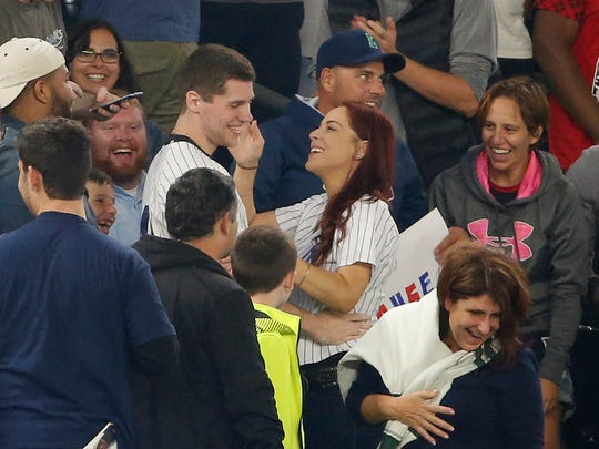 Fans laugh as Andrew Fox and Heather Terwilliger smile during a baseball game between the New York Yankees and the Boston Red Sox at Yankee Stadium in New York, Tuesday, Sept. 27, 2016. As Fox knelt to propose to Terwilliger, he pulled an engagement ring from his pocket - and it fell to the ground. The ring was found after a few minutes.