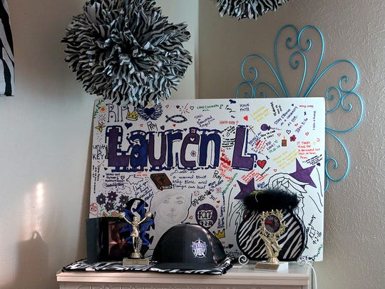 Messages left by friends of Lauren Landavazo sit on a poster displayed on her dresser in her bedroom.