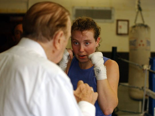 From left, Steve Acunto of Mount Vernon works with Fiona Koper of New Rochelle on her technique during a boxing class at Westchester Community College in Valhalla Oct. 27, 2004.