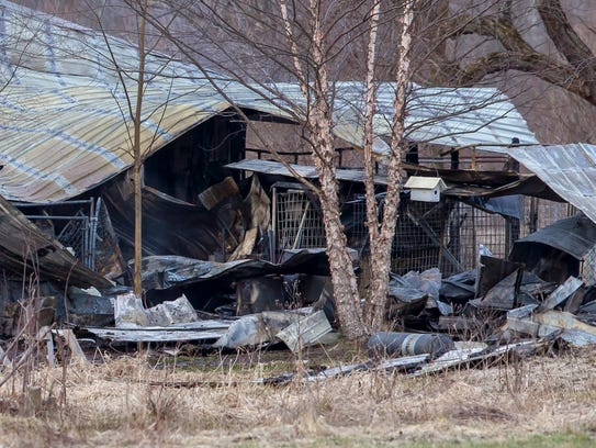 Charred debris lies in the aftermath of a fire at a boarding kennel in Fruitport Township, Mich., on March 30, 2018.