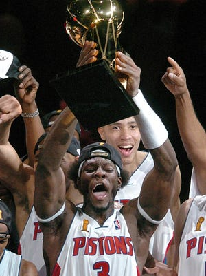 Ben Wallace holds the world championship trophy as the Pistons beat the Lakers in 2004.