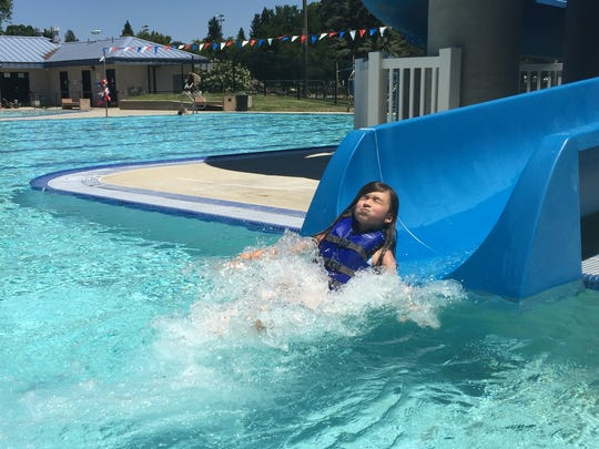 Tara Reuck, 8, slides into the water at the Redding Aquatic Center. The pool is a venue for kids enrolled in some of Redding Recreation's day camps.