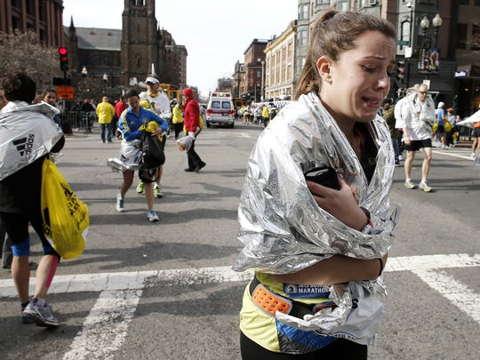 An unidentified Boston Marathon runner leaves the course crying near Copley Square following an explosion in Boston.