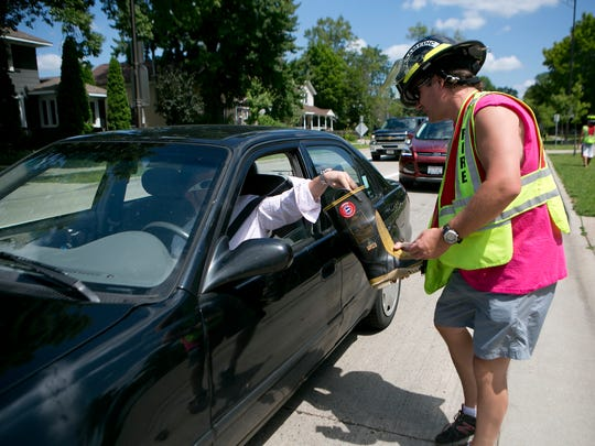 """Stevens Point firefighters collect donations during the """"Fill The Boot"""" campaign at the intersection of Division Street and Main Street in Stevens Point, Thursday, July 23, 2015."""