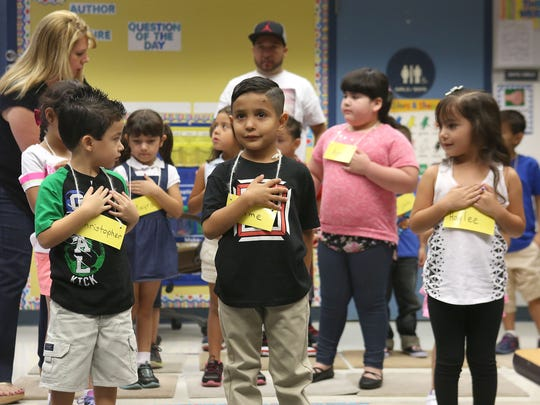 Kindergartners say the Pledge of Allegiance during the first day of school at John Adams Elementary School in La Quinta on Aug. 26, 2015.