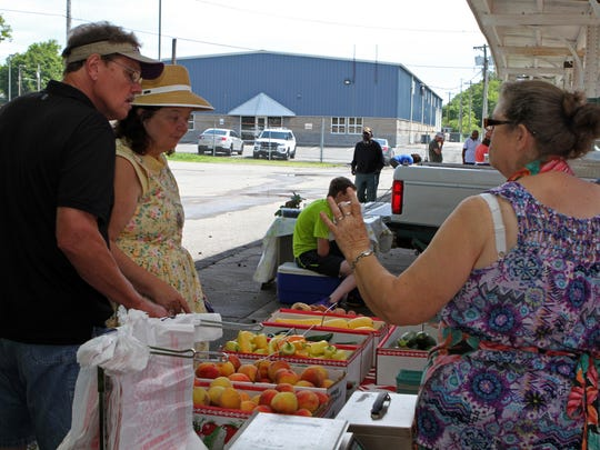 Jerry and Mary Goode, left, say they have been coming to the L & N Market twice a week for as long as they can remember. They were purchasing fresh produce from Judy Turner's table Saturday.