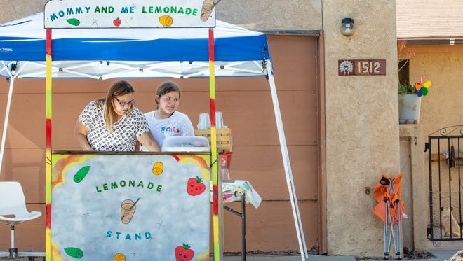 Nemiah Martinez, 11, works at her lemonade sStand with her mother Paloma by her side on Saturday, May, 5, 2018 in front of their home on Andrews Drive. Nemiah is raising funds to help pay for her mother's medical expenses. Her mother is in need of a new kidney and pancreas.