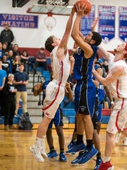 St. Clair High School's Matthew Eisenhardt (left) fights with players from Warren Woods Tower High School for a rebound during the MAC Gold Division championship basketball match at St. Clair High School Feb. 2.