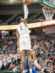 New Haven High School player Romeo Weems (1) jumps to dunk the ball during the MHSAA Class B basketball semifinals against Grand Rapids Catholic Central at the Breslin Center in East Lansing Friday, March 23.