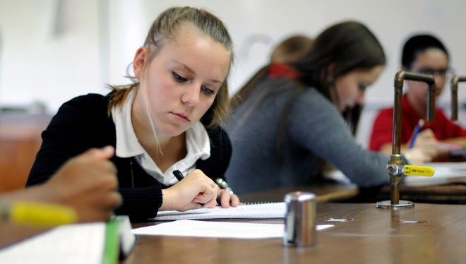 Lauryn Janski works on a biology assignment at Cardinal Mooney Catholic High School. Classes are canceled at Mooney because of a building problem.
