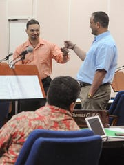 Sens. Brant McCreadie, right, and Michael San Nicolas celebrate with a fist bump after the passage of bills into law by lawmakers during session at the Guam Legislature in Hagåtña on Wednesday, Sept. 14.