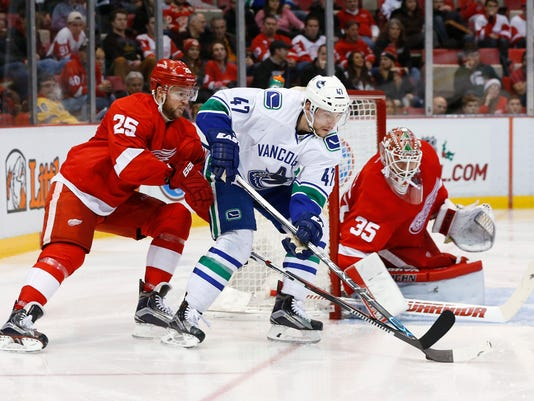 Detroit Red Wings goalie Jimmy Howard (35) stops a shot by Vancouver Canucks left wing Sven Baertschi (47) as Mike Green (25) defends in the second period of an NHL hockey game Friday, Dec. 18, 2015 in Detroit. (AP Photo/Paul Sancya)
