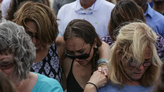 People bow their heads in prayer while gathered in the parking lot of the Berrien County Courthouse in St. Joseph on Tuesday July 12, 2016, before marching in memory of bailiffs Ron Kienzle and Joseph Zangaro from the Berrien County Courthouse after the bailiffs were shot and killed by inmate Larry Gordon on Monday at the courthouse.