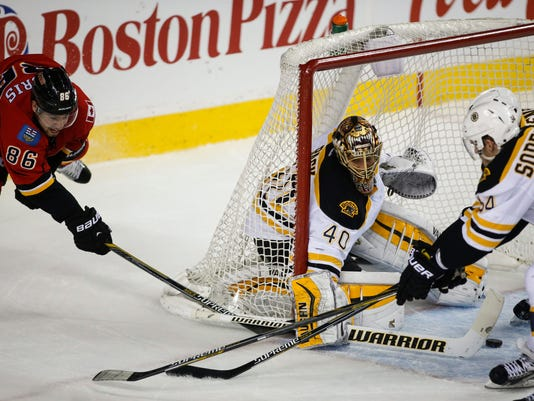 Boston Bruins goalie Tuukka Rask, center, from Finland, blocks the net as Calgary Flames Josh Jooris tries to score during first period NHL hockey action in Calgary, Alberta, Monday, Feb. 16, 2015. (AP Photo/The Canadian Press, Jeff McIntosh)