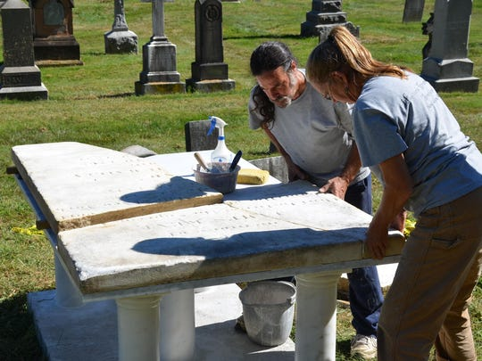 Ricardo Conde and Ta Mara Conde of Historic Gravestone Services place the pieces of the gravestone together during the restoration process.