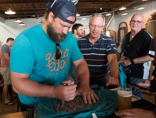 Pensacola native and Miami Dolphins football player, Josh Sitton, signs an autograph for Shawn Corliss during his visit to Perfect Plain Breweing in downtown Pensacola Friday, June 22, 2018.