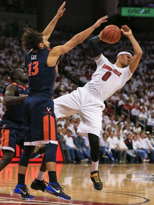 "Louisville's Damion Lee passes under Virginia defensive pressure Saturday afternoon at the KFC Yum! Center in downtown Louisville. Louisville lost 63-47. ""We got our brains beat in,"" said Pitino in the post-game press conference. Lee finished with six points. Jan. 30, 2016"