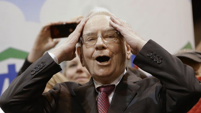 Berkshire Hathaway Chairman and CEO Warren Buffett  reacts at the newspaper throwing competition while touring the exhibition floor prior to the annual shareholders meeting on May 3, 2014, in Omaha, Neb.