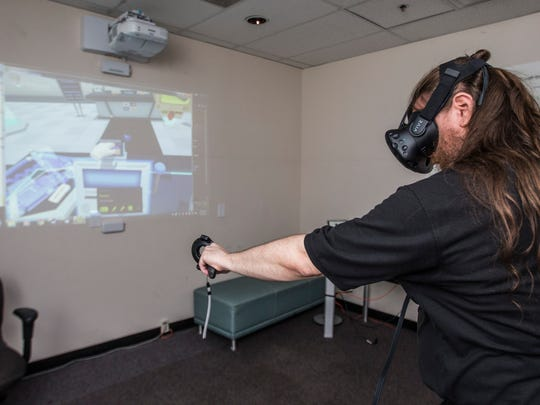 Derric Clark, program champion of game studies at the University of Advancing Technology in Tempe, demonstrates virtual-reality technology  on Sept. 1, 2016.