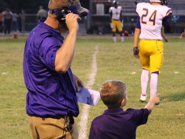 Logansport coach Kevin Magee, who quarterbacked the Tigers to a state title, gets a pointer from his son Kollin.