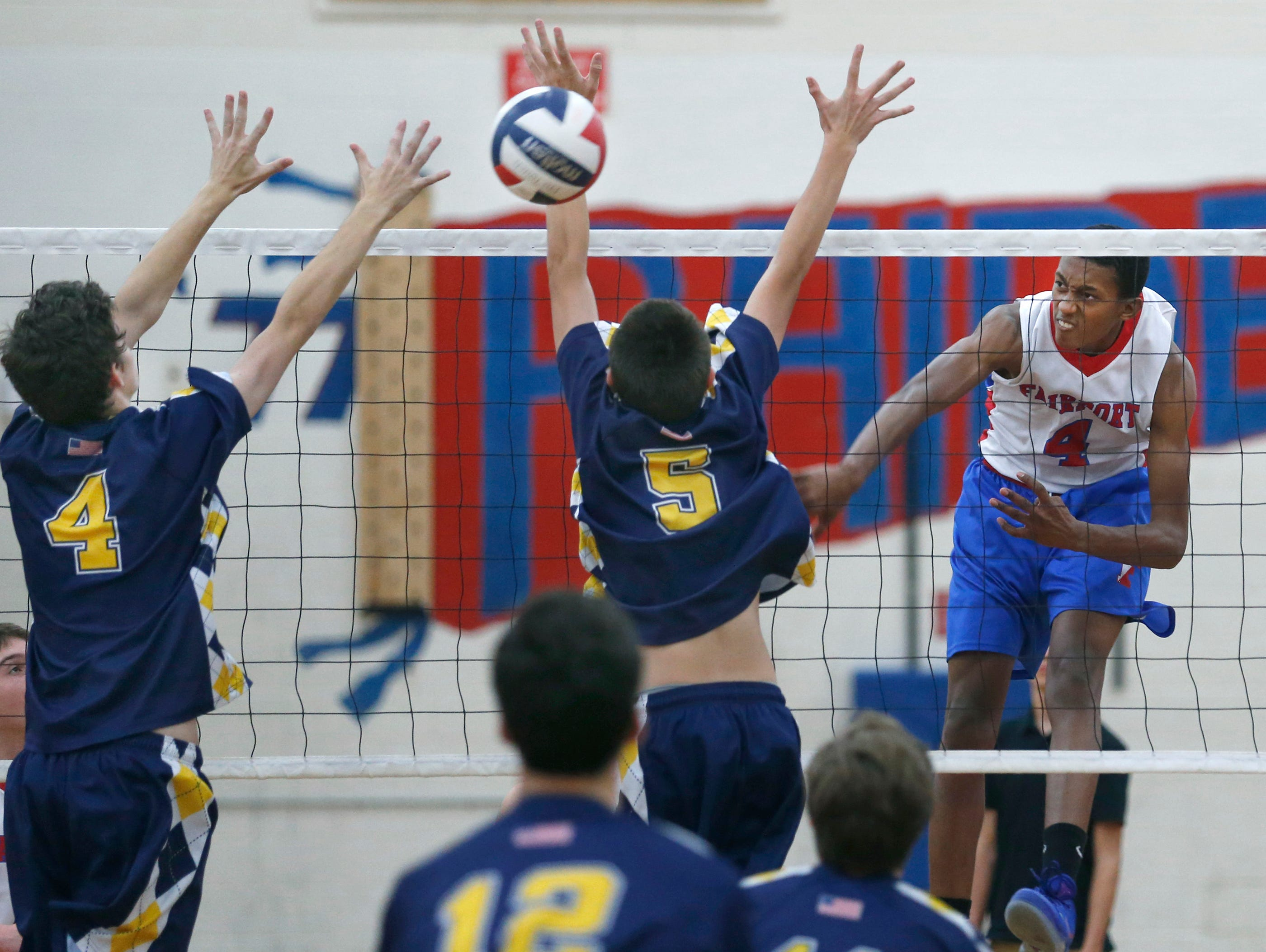 Fairport's Donovan Dey attacks against Victor's Hayden Hall and Cam Clark in the second set at Fairport High School.