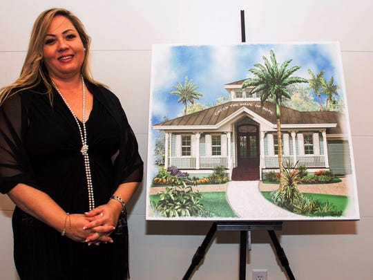 "Katerina Rosenblatt, guest speaker and author of of the book ""Stolen,"" with the artist's rendition of a home to house girls rescued from human trafficking. Money is being raised to pay to build the house."
