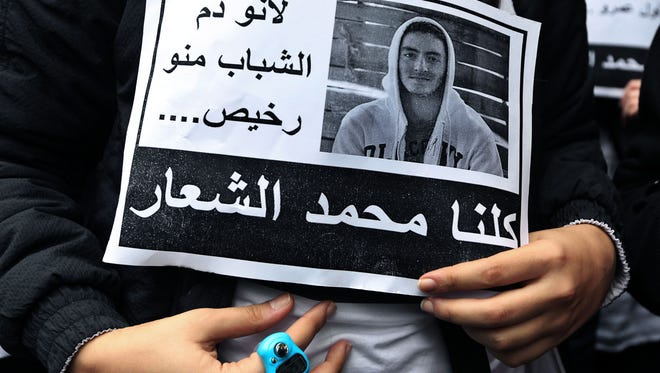 """A Lebanese student of the private Hariri High School holds a poster Dec. 30 with the photo of 16-year-old Mohammed Shaar, who was one of seven people killed in a car bomb that ripped through the upscale downtown district of Beirut. It reads in Arabic """"because the blood of youths is not cheap, we are all Mohammed Al-Shaar."""""""