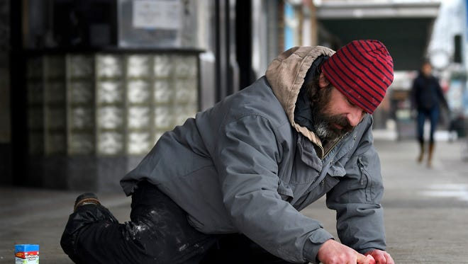 """In a Jan. 19 photo, 2018 photo, Avin Sigurani draws a koi fish on a sidewalk in Missoula, Mont., in an effort to convince passersby to leave a few coins to """"feed the fish."""" Sigurani has become somewhat of a well-known character downtown with his sidewalk drawing method of panhandling. (Kurt Wilson/The Missoulian via AP)"""
