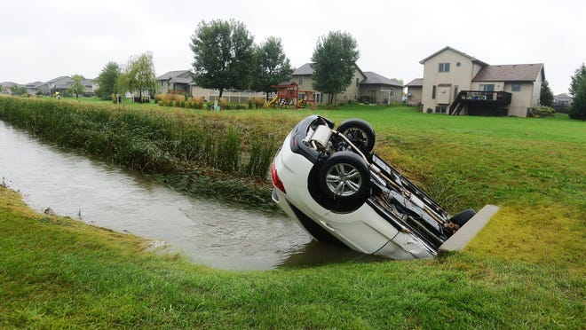 Car stuck in a culvert near Grinnell Avenue and Chesapeake Lane in western Sioux Falls following Thursday night's flash flood, Aug 28, 2015.