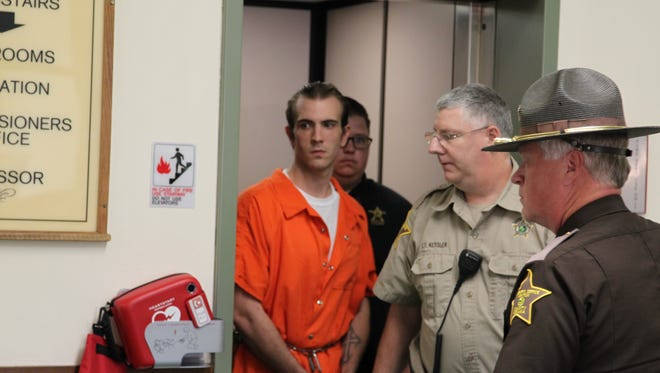 Derrick Cardosi, a man accused of an Aug. 28 triple homicide, is escorted to court Wednesday.
