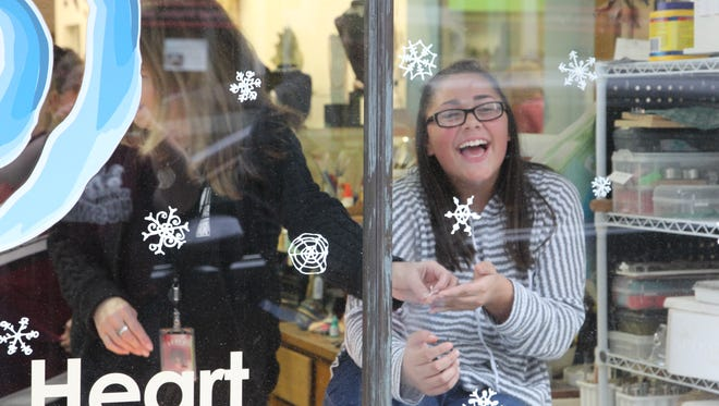 Alejandra Munoz, a Wea Ridge Middle School eighth-grader, clings handmade snowflakes to Grateful Heart's store front window.