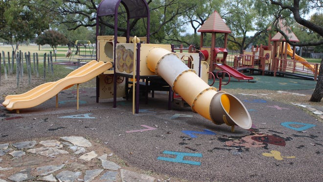 A photo taken in December 2016 shows part of the fall zone, a poured-in-place rubberized material to cushion falls, at Unidad Park are worn down, missing or cracked around the playground.