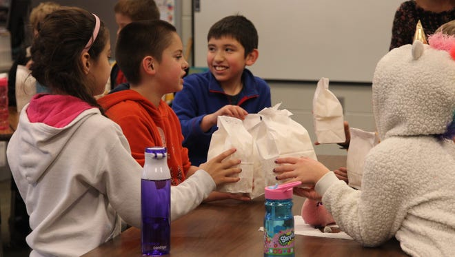 Students in Missy Buche's third grade class enjoy their popcorn treat while Buche read to them a chapter book.