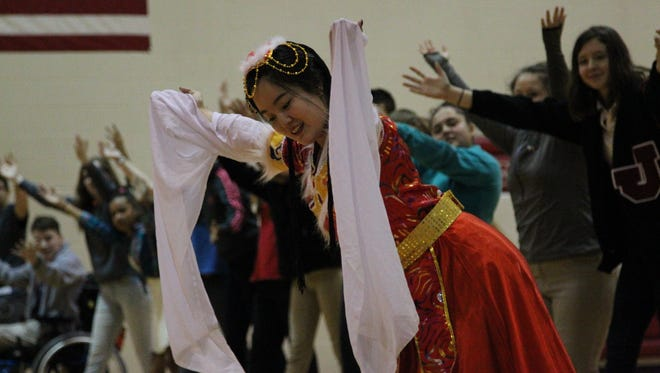 A performer teaches Tecumseh students how to bow like a traditional Chinese performer during Friday's Chinese New Year Celebration.