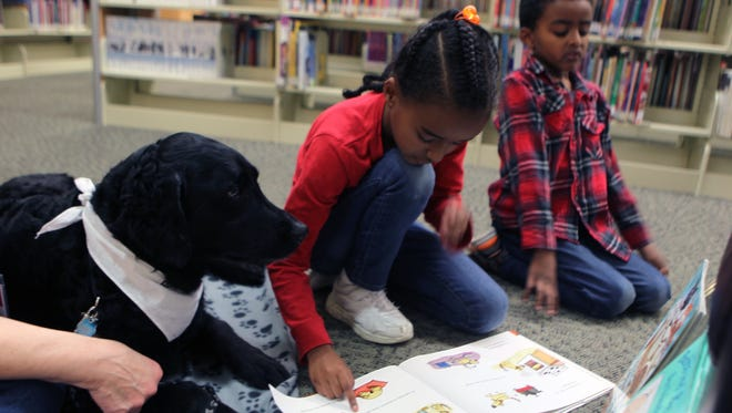 Martha Michael, 7, center, and Isaac Michael, 6, both of Redding, read with therapy dog Midnight during the Redding Library's 10th anniversary celebration in March.