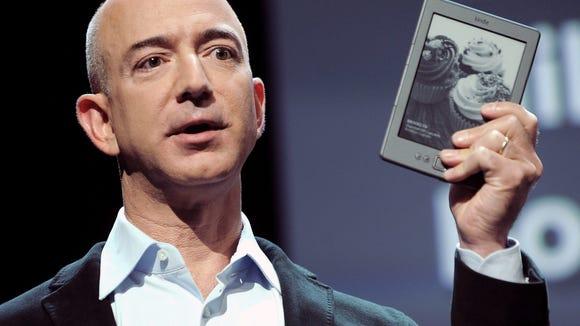 Jeff Bezos, CEO of Amazon.com, holding a  Kindle (EPA/JUSTIN LANE )