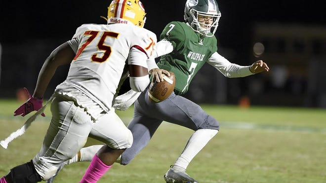 Greenbrier quarterback Brooks Pangle, right, tries to elude Clarke Central defender Jaquavious Cofer during football action at Greenbrier High School in Evans, Ga., Friday evening October 30, 2020.