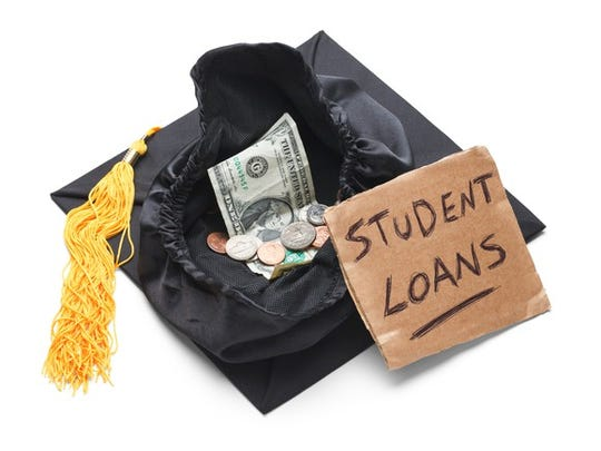 """A college graduation cap is filled with money, and a sign that says """"student loans"""" is placed in front of it."""