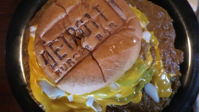 """The Burger Island at Old Detroit Burger Bar is a knife-and-fork sandwich, with a quarter-pound Angus beef patty smothered in coney sauce, onions, mustard and cheese sauce served in  the restaurant's signature """"branded"""" bun."""
