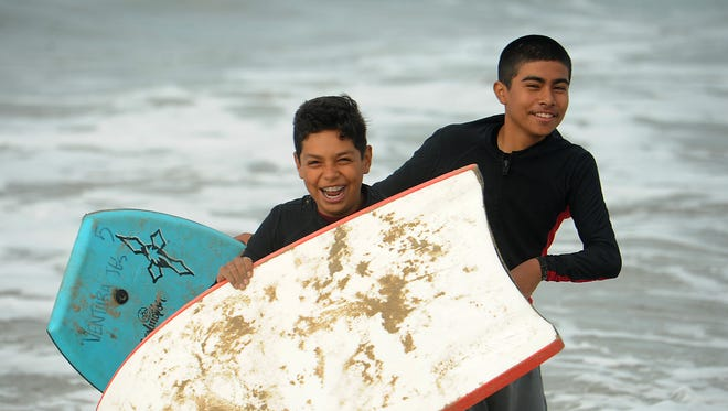 Adrian Ambriz (left) and Daniel Vasquez react to the cold water as they enjoy the day at the Marina Park beach in Ventura. The kids, from the Westpark Community Center, were taking part in the California State Parks program Surf Spot.