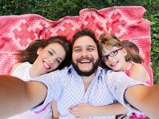 Summer scene of Happy young family taking selfies