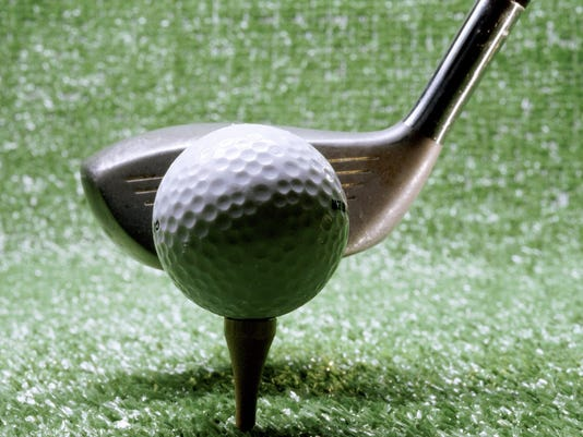 Close-up of a golf club next to a golf ball