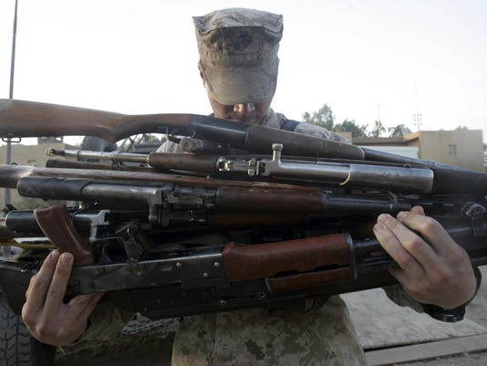 August 6, 2006 - A marine readies 80 pounds of enemy rifles seized.