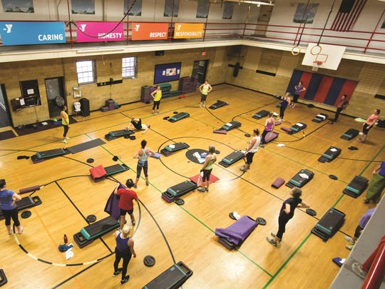The gym, used here for a group exercise class remains a hub of activity at the Y, with its core values of caring, honesty, respect and responsibility clearly on display.
