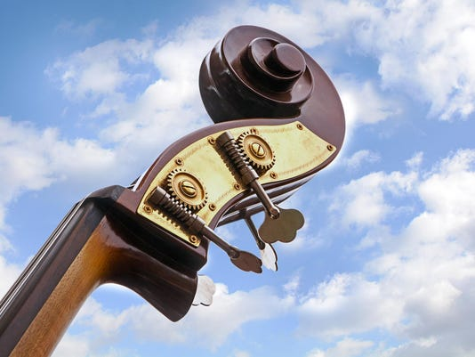 double bass, detail of the music instrument, blue sky, clouds