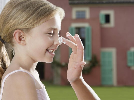 Mother applying sunscreen to daughter's (5-6) nose side view close-up of hand